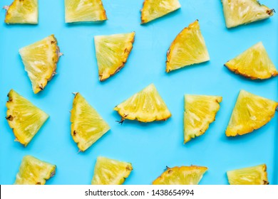 Fresh pineapple slices on blue background. Top view