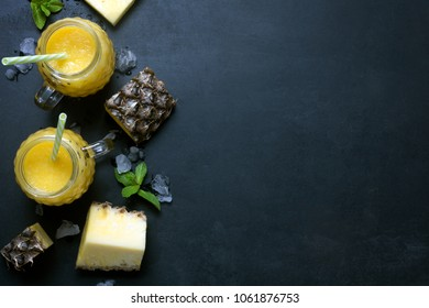 Fresh pineapple smoothie in glasses with fruits on a black rustic background. Flat lay and copy space with melted ice. Freshly blended summer drink nice to quench thirst during a hot day.