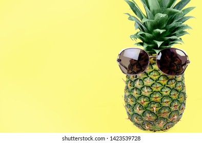 Fresh pineapple with sunglasses on yellow background