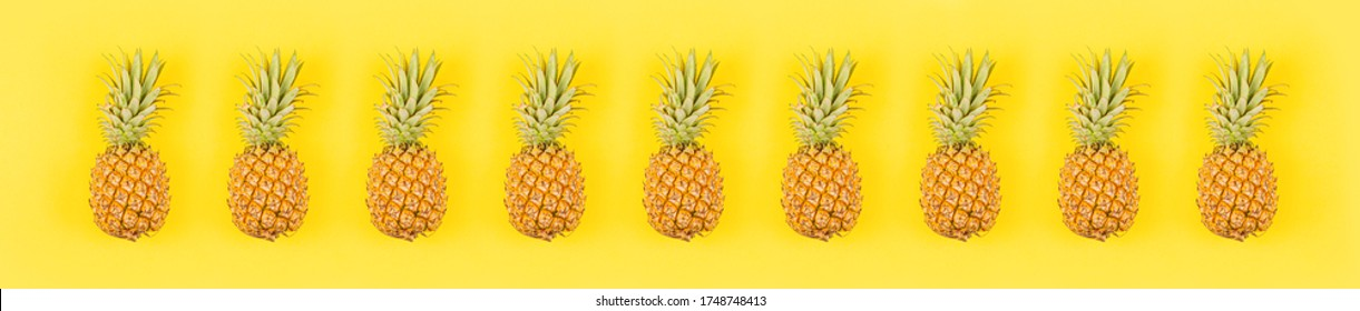 Fresh pineapples on yellow background. Top view, mockup, template, overhead. Summer concept. Creative flat lay. Horizontal long banner for web design