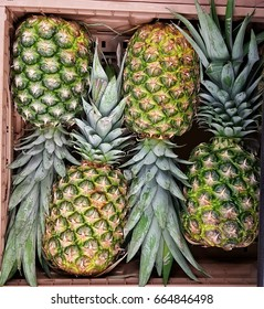 Fresh pineapples stacked in a carton
