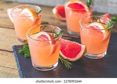 Fresh pink alcoholic cocktail with grapefruit, ice and rosemary, drink glass on a black stone board, old rustic style, selective focus, shallow depth of the field.