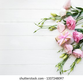 Fresh pink eustoma flowers and gift box on wooden background