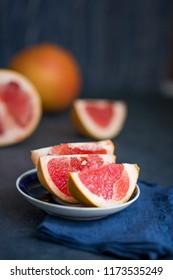 Fresh pink grapefruit slices on saucer on the blue background
