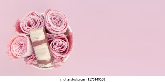 Fresh pink ice cream rolls. Top view of strawberry rolled ice cream with a piece of tasty chocolate bar in white chocolate.