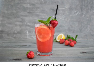 Fresh pink lemonade with lemon, lime and strawberries