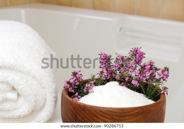 Fresh pink purple heather flowers in a teak wood bowl with epsom salts on the edge of a bathtub with a rolled up white towel ready to take a relaxing bath.