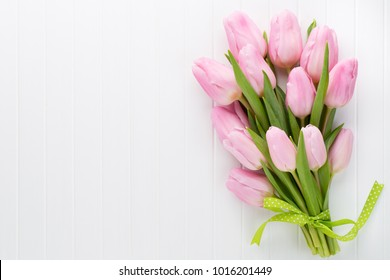 Fresh pink tulip flowers bouquet on shelf in front of wooden wall.