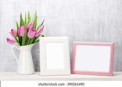 Fresh pink tulip flowers bouquet and blank photo frames with copy space on shelf in front of wooden wall