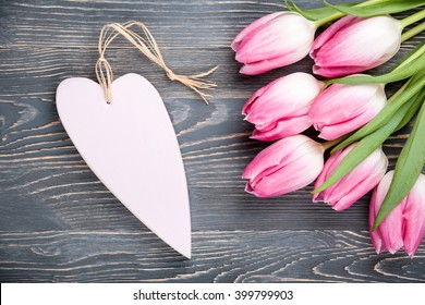 Fresh pink tulips and heart on wooden background