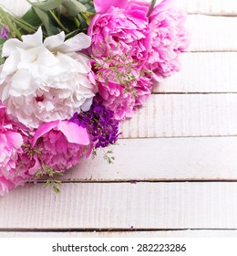 Fresh pink and white peonies flowers on white painted wooden planks. Selective focus. Place for text. Square image.