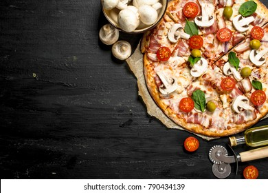 Fresh pizza with bacon, tomatoes, olives and greens. On the black chalkboard.