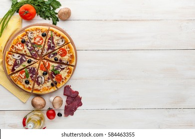 fresh pizza in a rustic Italian style with jerky olives mushrooms and three kinds of cheese on a light wooden background