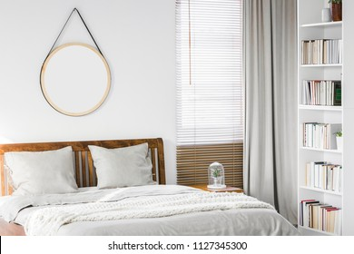 Fresh plant placed on bedside table next to king-size wooden bed in white room interior with window, round mirror and books