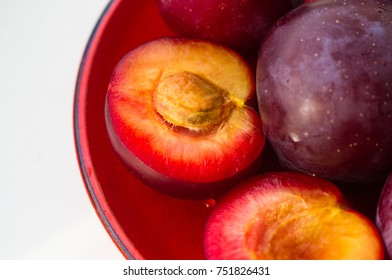 fresh plum fruit with cut plum slices in the red saucer on white background