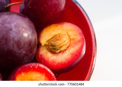 fresh plum fruit in the red saucer on white background