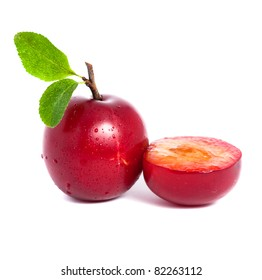 Fresh plum and a half with leafs isolated on white background
