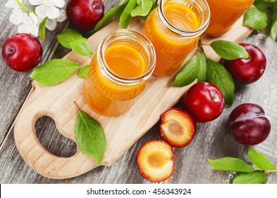 Fresh plum juice on the wooden table