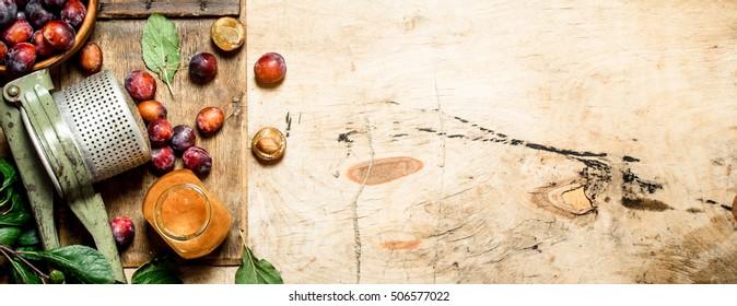 Fresh plum pulp in a glass jar. On wooden background.