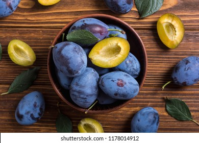 Fresh plums in bowl on wooden table . Fruit background