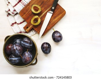 Fresh plums in bowl on wooden table, top view, copy space