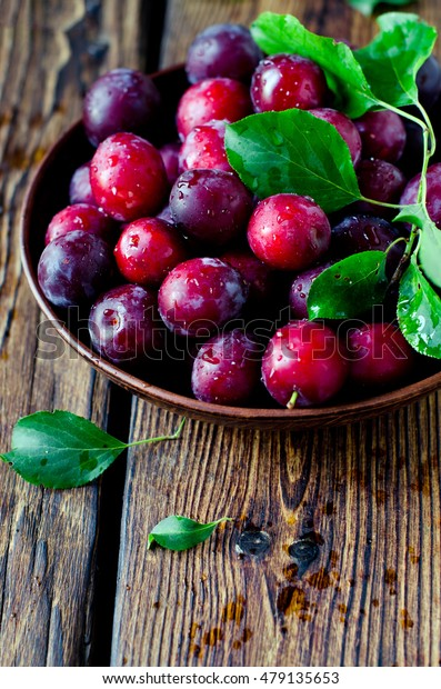 Fresh plums in a bowl on a wooden table