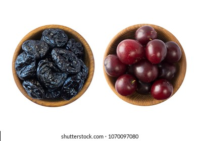 Fresh plums and dried prunes isolated on a white background. Dried prunes and fresh plums in a bowl on white background. Dried prunes and plums with copy space for text. Top view.