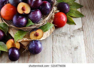 Fresh plums with leaves on a wooden table close up