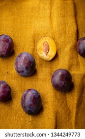 Fresh plums on yellow linen backdrop