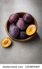 Fresh plums in wooden bowl