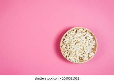 Fresh popcorn bowl isolated on pink background top view. Frame composition with copy space.