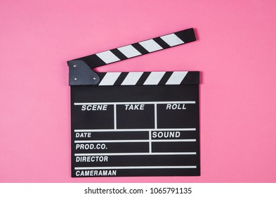 Fresh popcorn and movie clip isolated on pink background top view with copy space around products. Cinematic concept for blogs or design