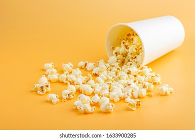 Fresh popcorn spilled out of the white box on a orange background. Cinema snack concept. The food for watching a movie and entertainment. Copy space for text, close up. Popcorn box mocap