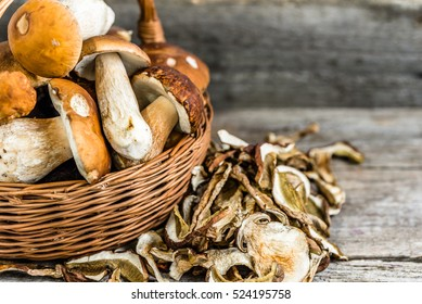 Fresh porcini mushrooms in a basket and dried mushrooms on wooden table