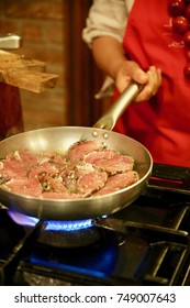 Fresh pork slices being sautéed in a skillet topped with fresh herbs and spices.