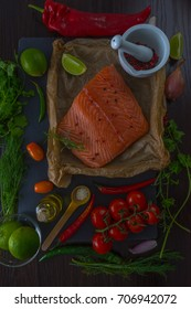 Fresh portion of fresh salmon fillet with aromatic herbs, spices and vegetables. Healthy food. Top view.