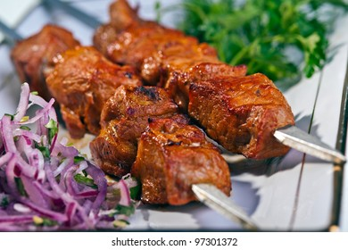 fresh portion of shish kebab on plate with onion and greens