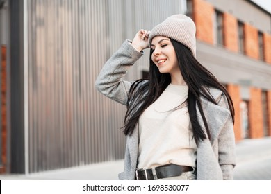 Fresh portrait charming joyful young woman with beautiful smile with long hair in fashionable youth clothes on street in the city. Positive attractive girl model is walking and smiling on spring day.