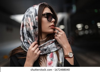 Fresh portrait young attractive woman with clean healthy skin with sexy lips in trendy sunglasses in coat with elegant silk scarf on head in the city. European business girl fashion model. Retro style
