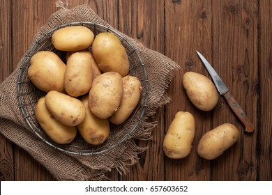Fresh potatoes in basket on old wooden background. Top view