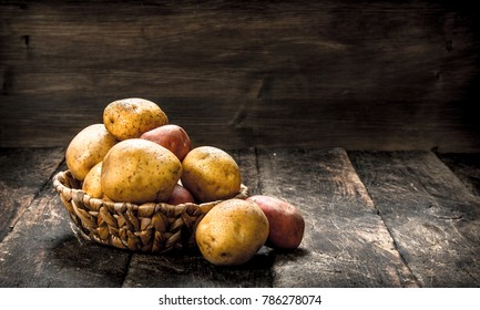 Fresh potatoes in a basket. On a wooden background.