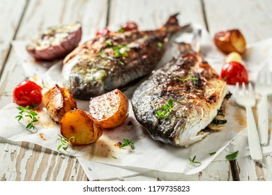 Fresh potatoes and seabream with herbs and tomatoes