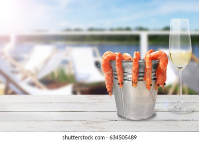 Fresh prawns on wooden table by the sea.