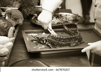 Fresh prepared fish sterlet in a metal oven of restaurant kitchen. Selective focus. Shallow depth of field. Toned.