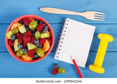 Fresh prepared fruit salad, dumbbells for using in fitness and notepad for writing notes or resolutions, concept of sport, diet, slimming, healthy lifestyles and nutrition