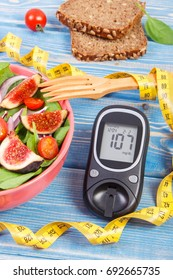 Fresh prepared fruit and vegetable salad, glucose meter with result of measurement sugar level and tape measure, concept of diabetes, diet, slimming, healthy lifestyles and nutrition