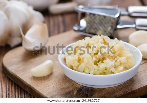 Fresh pressed Garlic (detailed close-up shot) on rustic wooden background