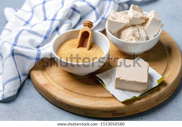 Fresh pressed yeast and dry soluble yeast on wooden serving board, selective focus.