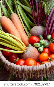 Fresh produce from a vegetable garden gathered in a rustic wicker basket - carrots, beetroot, beans, cucamelons and red tomatoes