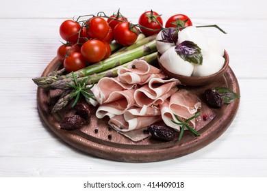 Fresh prosciutto with basil and mozzarella
